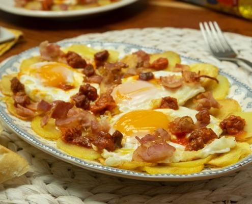 Patatas con huevos fritos, bacon, sobrasada y miel